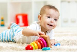 Malutkie dziecko leżące na brzuszku bawiące się ręką zabawką wieżą